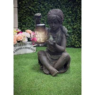 Weathered Girl Sitting with Solar Lantern Holding a Frog